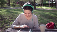Young woman cheers up while listening music on tablet - stock footage