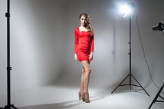 Young model in red dress posing in spotlight Stock Photos
