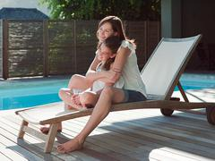 Girl and mother on lounge chair by swimming pool - stock photo