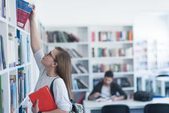 famale student selecting book to read in library - stock photo
