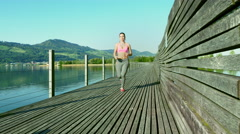 Young woman runs on the steg Stock Footage