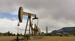 Oil well pumping with power plant in back on cloudy day Stock Footage