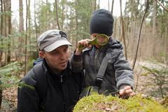 Father and son using loupe - stock photo