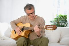 Man strumming guitar - stock photo