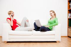 Two women using laptop and phone on sofa Stock Photos
