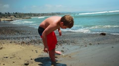 Slow motion of kid standing in front of the ocean playing with sand - stock footage
