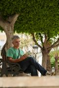 Man sitting on bench reading guidebook - stock photo