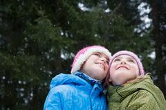 Girls looking up at snowflakes Stock Photos