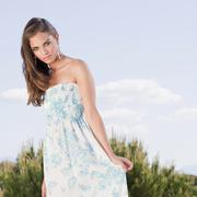 Beautiful young woman in flowery dress - stock photo