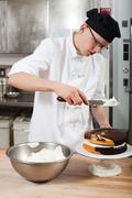 Male chef icing a cake in commercial kitchen Stock Photos