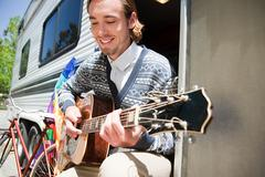 Young man playing guitar by caravan - stock photo