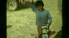 1977: Poor young street child excitedly waving hello yelling working on tips. Stock Footage