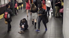 woman giving homeless man change in his cup in subway NYC 4K and 1080 HD - stock footage