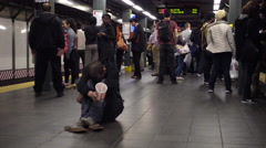 homeless man sitting on subway station platform floor in 4K and HD NYC - stock footage