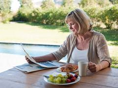 Woman outdoors with breakfast and newspaper Stock Photos