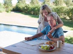 Couple outdoors with breakfast and newspaper Stock Photos