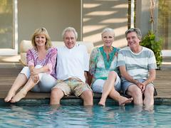 Mature friends by swimming pool - stock photo