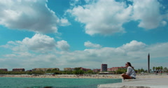 People relax on Barcelona beach. Time lapse of white clouds on sky over blue sea - stock footage