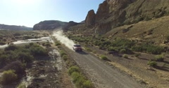 Aerial scene of car traveling on dirt road a dry, rocky, landscape. Monumental s Stock Footage