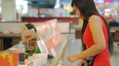 Young Asian Lady taking food in foodcourt 4k UHD (3840x2160) - stock footage