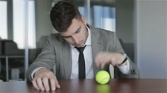 Sad businessman meditates looking on the spinning ball. Stock Footage