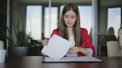 Two business women are working in office. The girl in red jacket reads documents Stock Footage