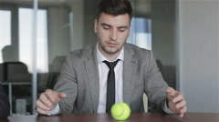 Sad man in a gray jacket ponders future of business rolling a tennis ball. - stock footage