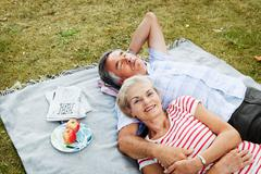 Couple laying on picnicblanket in grass Stock Photos