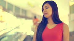 Woman standing on escalator in mall toned video Stock Footage