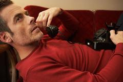 Man on couch using vintage phone - stock photo
