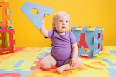 Baby girl playing with toy alphabet letters - stock photo