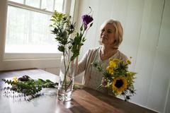 Mature woman arranging flowers - stock photo