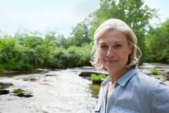 Mature woman in rural scene - stock photo
