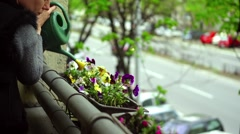 Watering flowers on a balcony Stock Footage