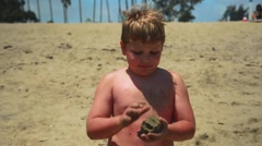 Slow motion of young boy standing at beach playing with sand Stock Footage