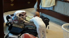 Toddler Trying To Pack Suitcase Stock Footage