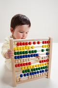Baby boy playing with abacus - stock photo