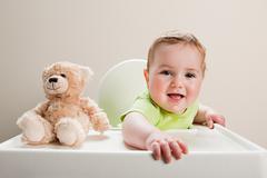 Baby boy sitting in highchair with teddy bear - stock photo