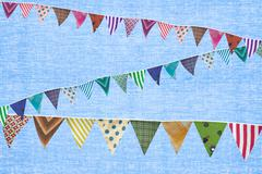 Multi coloured bunting against blue background - stock illustration