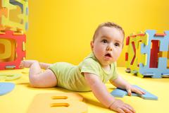 Baby boy playing with toy alphabet letters - stock photo