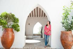Young woman standing by archway Stock Photos