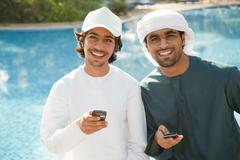 Two Middle Eastern men with mobile phones - stock photo