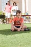 Young boy in the garden with parents - stock photo