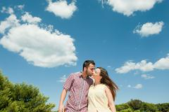 Affectionate young man kissing girlfriend - stock photo