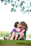Two women kissing in park Stock Photos