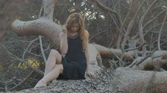 Girl sitting on a fallen pine tree in the evening Stock Footage