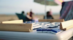 Cool close-up of Dominoes on a table at beach with people in the background Stock Footage