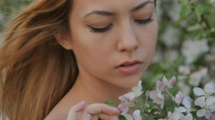 Blonde girl looking at the blooming apple tree branch Stock Footage