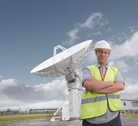 Worker in front of satellite dish Stock Photos
