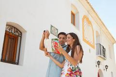 Couple reading guidebook by old church - stock photo